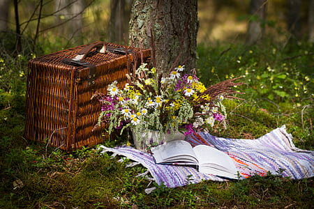 brown picnic basket and flower arrangement