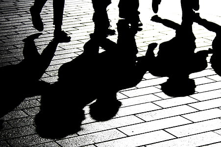 silhouette of group of people on brick floor