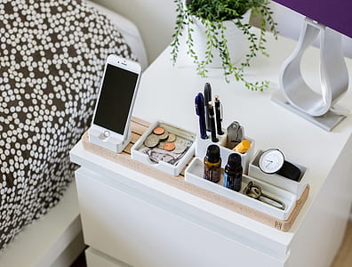 silver iPhone 6 on white holder beside coins and pens on white wooden nightstand