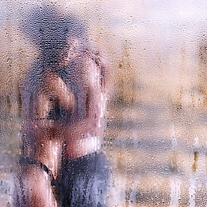 man and woman kissing behind glass window