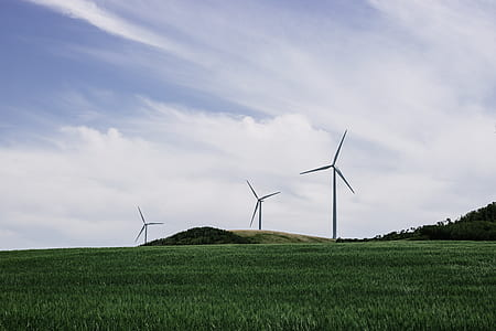 three gray wind turbines on green grass field