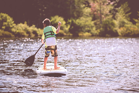 boy in green vest on white and black paddle boat on body of water during daytime