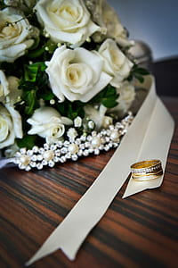 gold-colored clear gemstone encrusted ring on white ribbon near bouquet of white roses