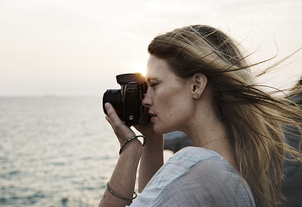 woman taking photograph on body of water at daytime