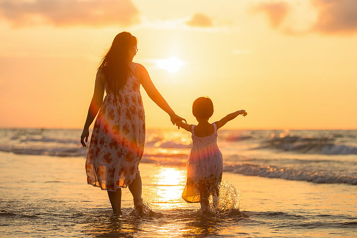 woman wearing white and red sleeveless dress walking with girl on sea shore during sunset