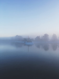 white watercraft on top on body of water with fogs