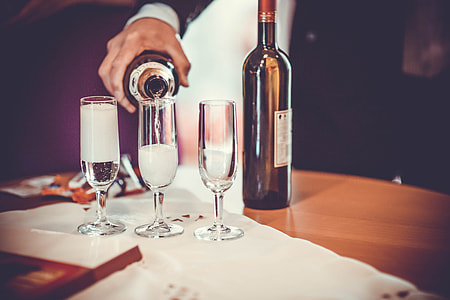 A man pours champagne into drinks glasses