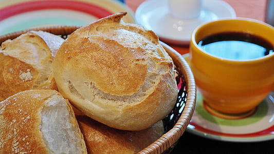 bread on bowl beside cup of cuffee