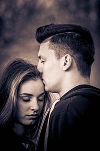 sepia photo of man kissing woman's head