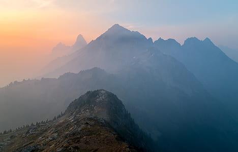 black mountain with fog under golden hour