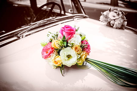 white, yellow and pink rose bouquet on car