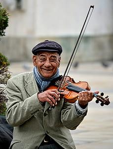 man using violin smiling