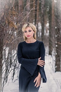woman in black long-sleeved dress surrounded of bare tree during daytime