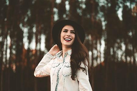 woman wearing black hat and denim jacket laughing