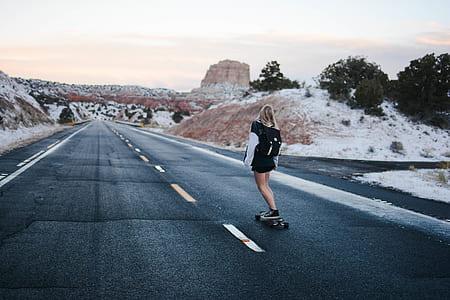 woman in black riding a skateboard