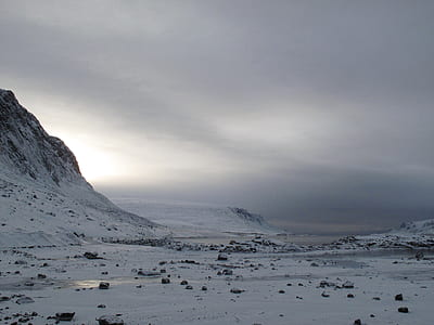 snow covered terrain with mountains under gray sky