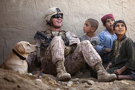 soldier sitting beside three children and adult yellow Labrador retriever