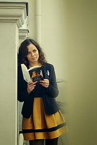 woman wearing black and yellow dress and holding a book