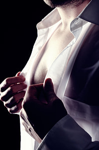 man buttoning up white dress shirt