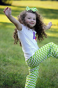 girl in white shirt and green chevron pants doing dance moves during daytime
