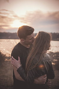 man kissing woman near body of water during sunset