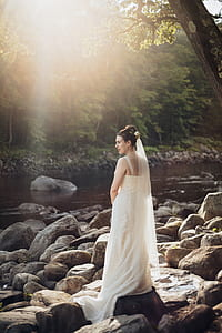 woman wearing white sleeveless wedding gown standing on rocks near body of water