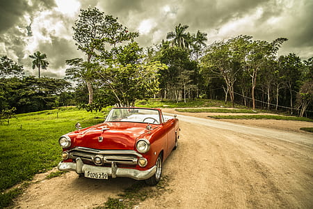 red convertible coupe on road under white sky