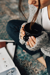 Woman reading magazines on the floor while enjoying her cup of tea