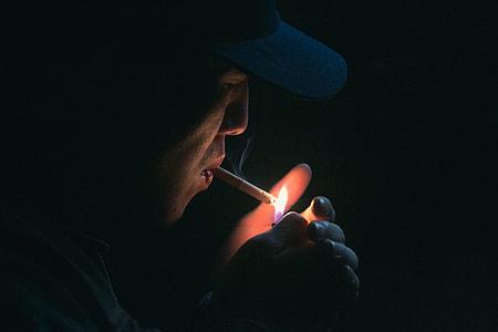 smoking man in black cap