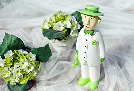 man wearing white suit figurine on white mesh cloth