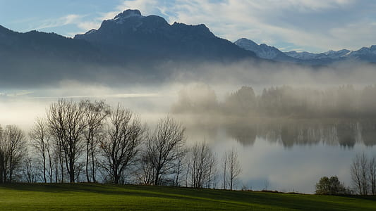 body of water covered with fog near mountain range