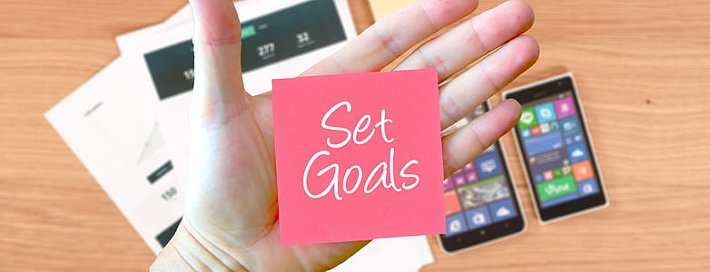 set goals signage on human palm