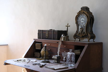 brown wooden analog clock on top of brown wooden slant-top desk near the wall