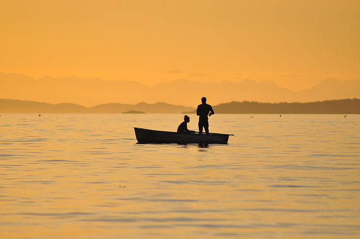 silhouette photo of two person on boat surrounded body of water
