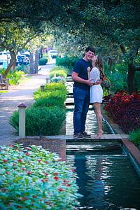 Woman and Man Standing on Bridge Kissing