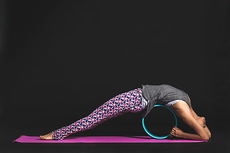 person in grey tank top and pink leggings on teal pipe and pink yoga mat