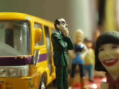 shallow focus photography of man in green suit coat plastic toy