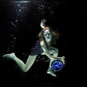 woman wearing black dress holding clock