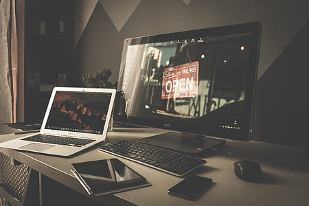 black flat screen computer monitor and gray laptop computer