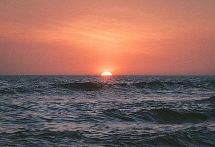 orange sky over waving ocean during sunset