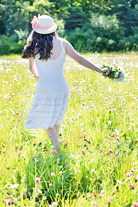woman in white spaghetti strap dress on green-and-pink flower field during daytime