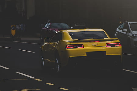 yellow Chevrolet Camaro at the city road