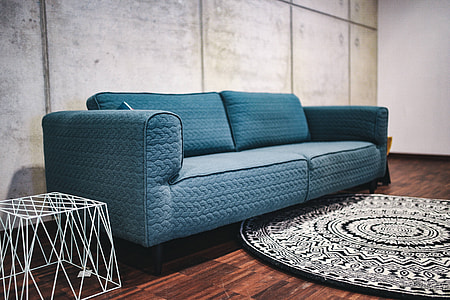 Blue sofa with pillows in a designer living room interior