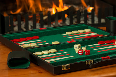 green, red, and white backgammon board on brown wooden tabletop