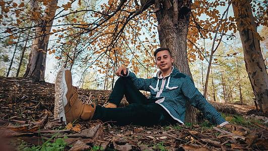 Man Wearing Green Jacket Sitting on Ground Near Tree