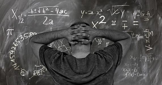 man wearing gray shirt facing on blackboard