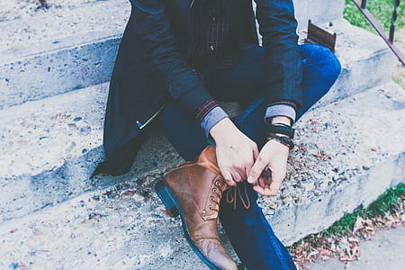 person wearing blue jeans and brown boots