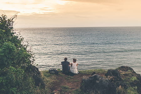 man and woman sitting on cliff near wave of sea