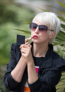 Blond Short Haired Woman Applying Pink Lipstick Outside