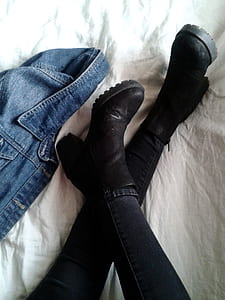 person wearing pair of black leather chunky-heeled boots